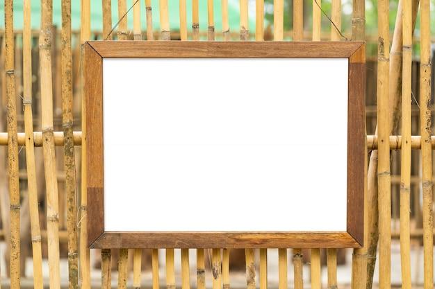Leerer weißer hölzerner fotorahmen auf bambuswand