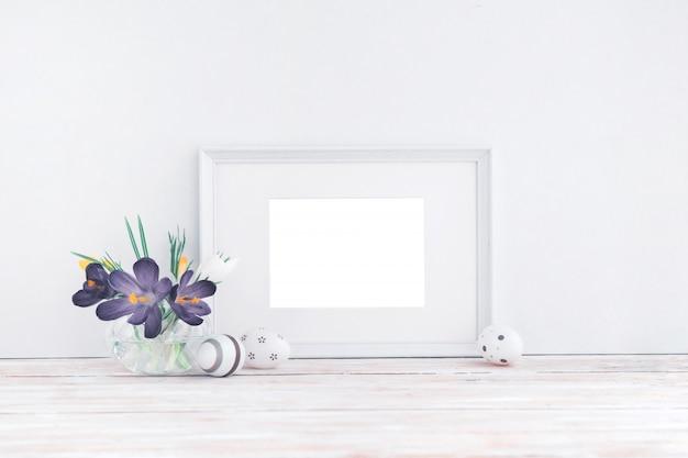 Leerer weißer holzrahmen, blumen und dekorative eier auf weißem hintergrund mit kopienraum. attrappe, lehrmodell, simulation.
