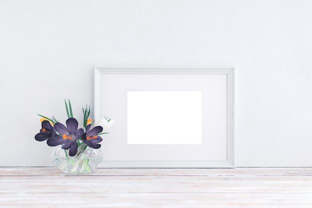 Leerer weißer holzrahmen und blumen im vase auf weißem hintergrund mit kopienraum. attrappe, lehrmodell, simulation.