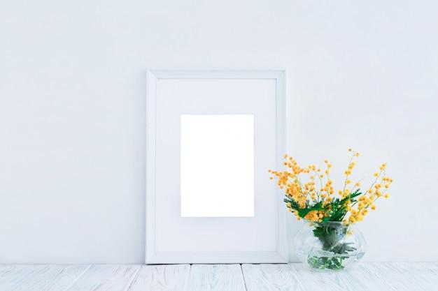 Leerer weißer holzrahmen und gelbe mimosenblumen mit kopienraum. attrappe, lehrmodell, simulation.