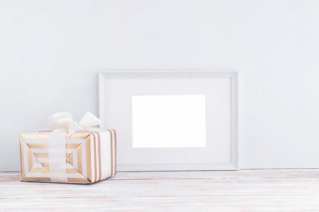 Leerer weißer holzrahmen und geschenkbox mit band auf weißem hintergrund mit kopienraum.