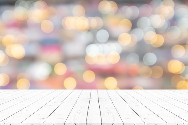 Leerer weißer holztisch der perspektive auf die oberseite über unschärfehintergrund, kann verwendet werden, um für montageproduktanzeige oder entwurf zu verspotten.