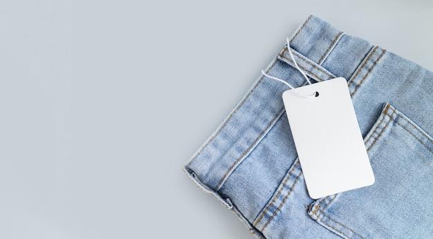 Leerer weißer kartonanhänger oder etikett mit seil auf jeanskleidungshintergrund