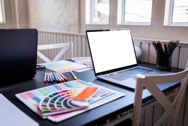 Leerer weißer laptopschirm von grafikdesignern setzte an schreibtischtabelle in das mitarbeiten ein