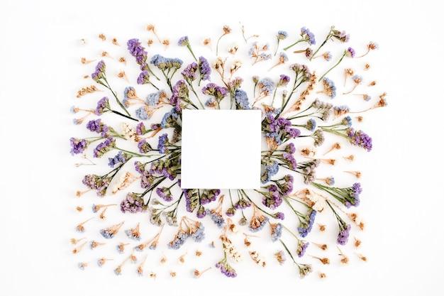 Leerer weißer papierleerer auf blauem und purpurrotem getrocknetem blumenrahmen auf weißem hintergrund. flache lage, ansicht von oben