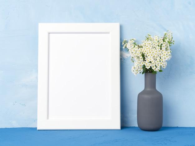 Leerer weißer rahmen, blume im anstarren auf dunkelblauer tabelle gegen blaue betonmauer