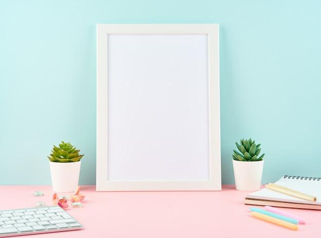 Leerer weißer rahmen des modells, warnung, notizblock, tastatur auf rosa tabelle gegen blaue wand mit kopie. moderner heller bürodesktop