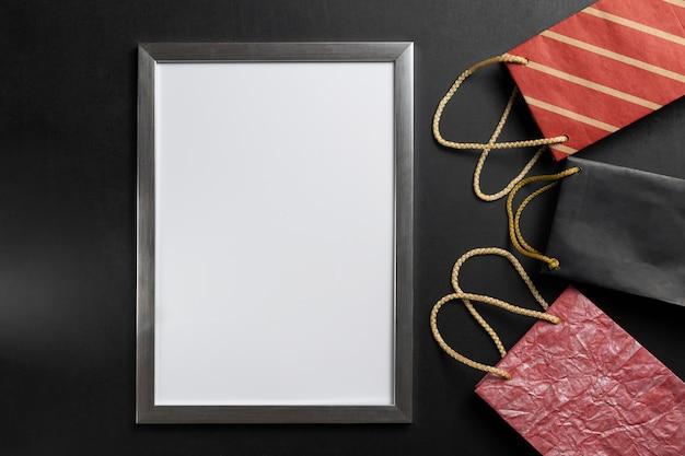 Leerer weißer rahmen mit copyspace und festlichen papiertüten