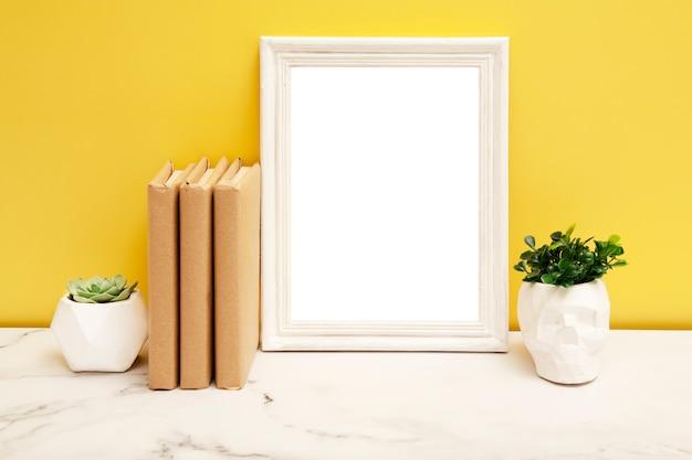 Leerer weißer rahmen mit einem hauptpflanzen und bücher auf dem tisch auf gelbem hintergrund