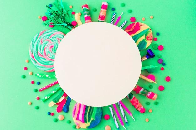 Leerer weißer rahmen über partyzubehör und -süßigkeiten auf grünem hintergrund