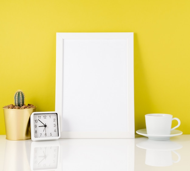 Leerer weißer rahmen, uhr, sukkulente, becher tee oder kaffee wieder