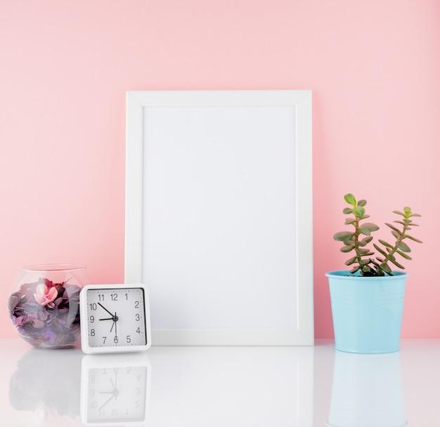 Leerer weißer rahmen- und betriebskaktus, auf einer weißen tabelle gegen die rosa wandkopie
