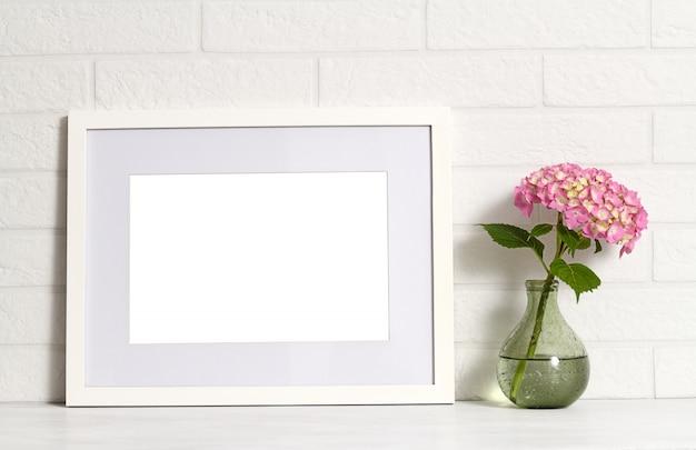 Leerer weißer rahmen und hortensienblume in der vase