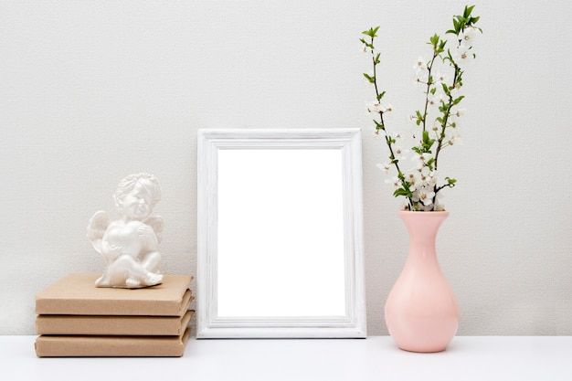 Leerer weißer rahmen verspotten mit rosa vase und büchern auf dem tisch. holzrahmen für ihren text.