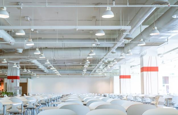 Leerer weißer stuhl und tisch in der cafeteria des einkaufszentrums. luftkanal, klimaanlagenrohr und sprinkleranlage. belüftungssystem. gebäudeinnenraum. deckenleuchte licht.
