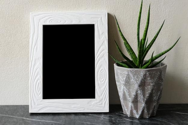 Leerer weißer vintage-holzrahmen, der über weißer zementwand und schwarzem marmorboden mit schattenhintergrund steht, kopierraum für mock-up und vorlage