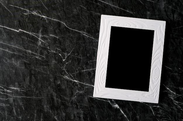 Leerer weißer weinleseholzrahmen auf schwarzem marmorhintergrund