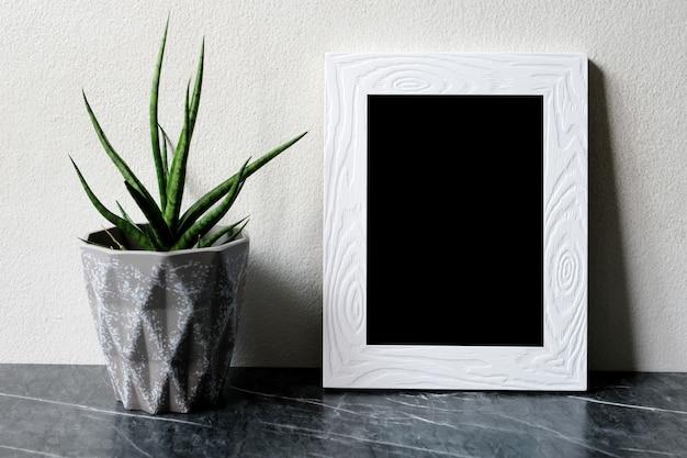 Leerer weißer weinleseholzrahmen, der über weißer zementwand und schwarzem marmorboden mit schatten steht
