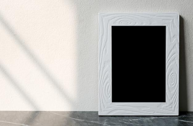 Leerer weißer weinleseholzrahmen, der über weißer zementwand und schwarzem marmorboden mit schattenhintergrund steht