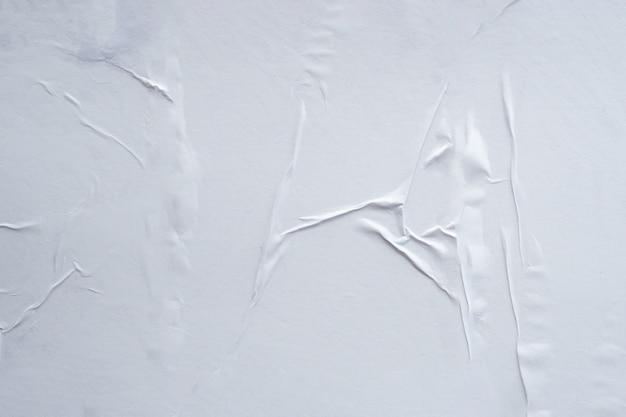 Leerer weißer zerknitterter und gefalteter papierplakatbeschaffenheitshintergrund