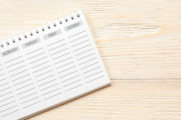 Leerer wochenplaner auf weißem bürotisch, wochenendkonzept