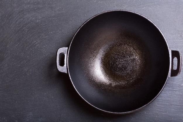 Leerer wok in einem dunklen hintergrund, draufsicht