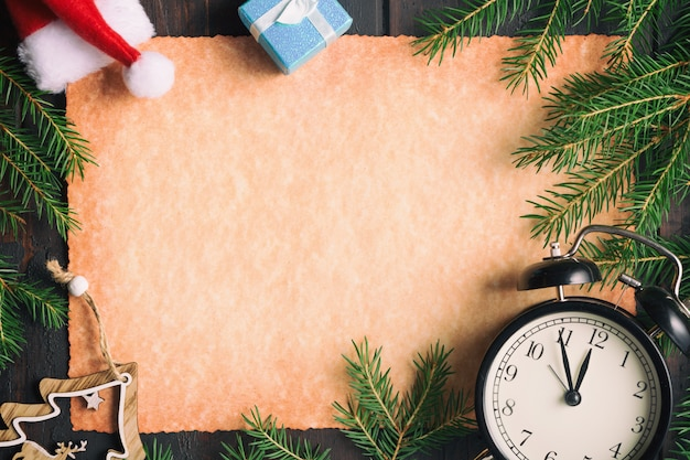 Leeres altes papier mit weihnachtstannenbaumasten mit weinlesewecker, geschenkboxen und sankt-hut.