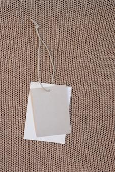 Leeres beige kleideretikett-etikettenmodell auf gestrickter textiloberfläche