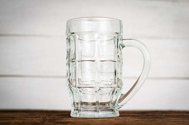 Leeres bier pint, becher auf holztisch.