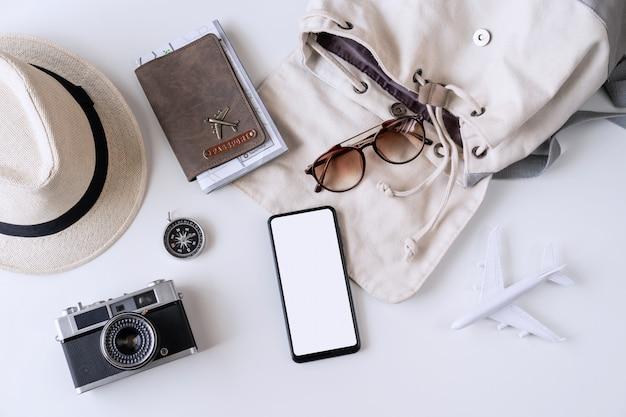 Leeres bildschirm-smartphone mit reisezubehör und -artikeln, reiseplanungskonzept