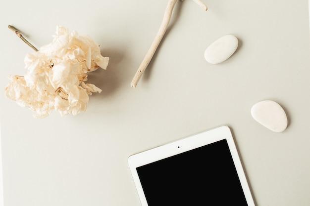 Leeres bildschirmtablett mit kopierraum, steinen, zweig, hortensienblume