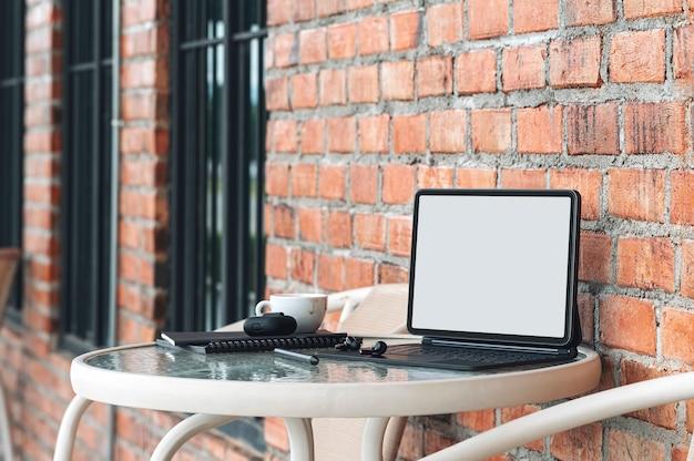 Leeres bildschirmtablett mit magischer tastatur und gadget am runden tisch im café im freien.