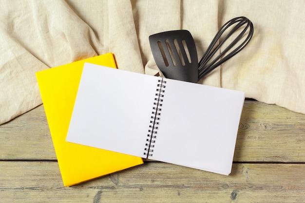 Leeres blatt des geöffneten notizblockes und der küchengeräte auf tabelle mit tischdecke, kopienraum