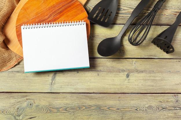 Leeres blatt des geöffneten notizblockes und der küchengeräte auf tabelle mit tischdecke