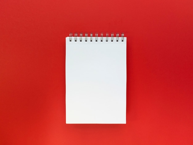 Leeres blatt des roten hintergrunds des notizbuchs. bildungskonzept. flach mit kopierraum liegen.