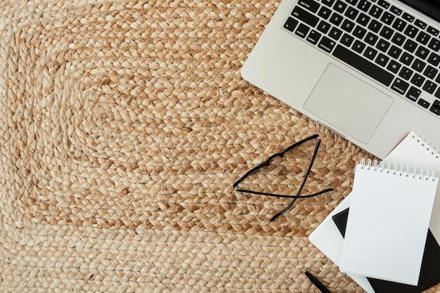 Leeres blatt notizbuch, laptop, brille, stift auf korbstroh