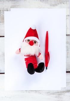Leeres blatt papier auf dem holztisch mit einem stift und dem weihnachtsmann.