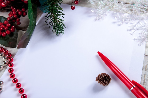 Leeres blatt papier auf dem holztisch mit einem stift und weihnachtsdekorationen.
