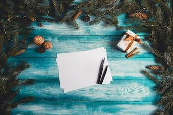 Leeres Blatt Papier auf einem blauen Holztisch mit Weihnachtsartikeln. Weihnachts-Konzept.