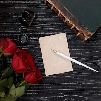 Leeres blatt papier des schönen weinlesehintergrundes mit einem badstift, einem tintenfass, einem alten buch und drei roten rosen auf einem abgenutzten schwarzen hölzernen hintergrund, einer ansicht von der spitze oder einer ebenenlage