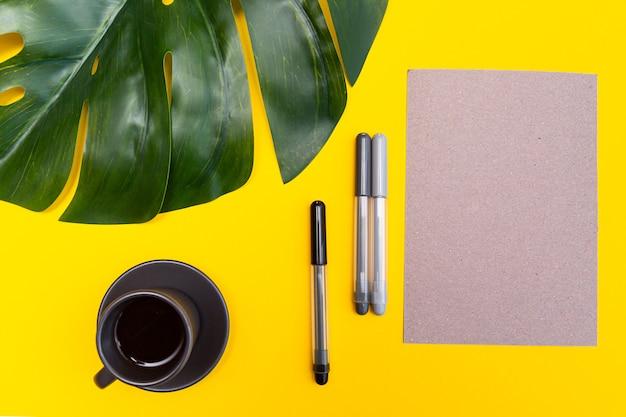 Leeres blatt papier, filzstifte, monstera-blatt und eine tasse schwarzen kaffee auf einem gelben