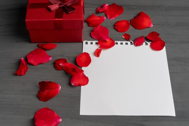 Leeres blatt papier für text und rote geschenkbox nahe bei einem blumenstrauß und roten rosafarbenen blumenblättern