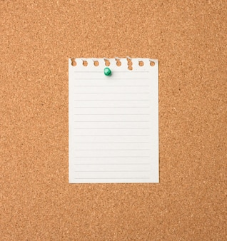 Leeres blatt papier mit knopf auf braunem balsa-brett, kopierraum
