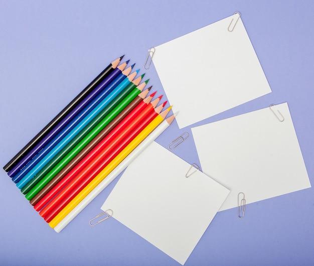Leeres blatt papier und farbstifte auf violett für projekte und ankündigungen