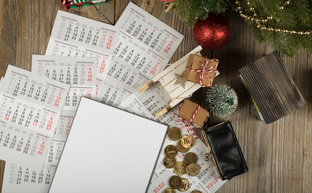 Leeres blatt papier und kleine geldbörse mit münzen auf dem neujahrshintergrund draufsicht