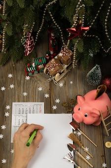 Leeres blatt papier und rosa sparschwein auf einem neujahrshintergrund draufsicht