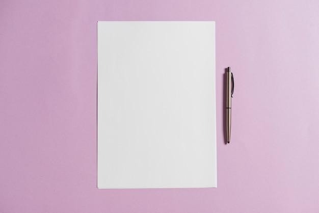 Leeres blatt papier und stift auf rosa hintergrund