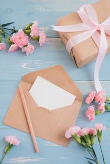 Leeres blatt papier zur begrüßung von text und geschenkbox. draufsicht. flach liegen.