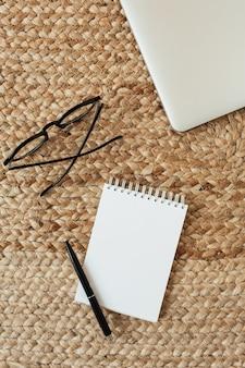 Leeres blattheft mit kopierraum, brille, stift, laptop auf weidenstroh