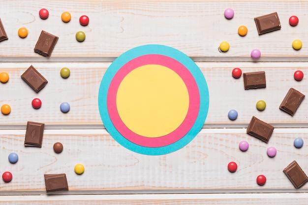 Leeres blau; rosa und gelber kreisrahmen mit süßigkeiten auf hölzernem schreibtisch